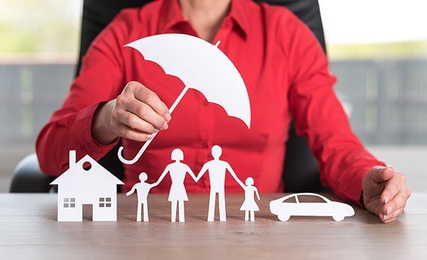 Acosta Law Firm asset protection. Business woman sitting at desk holding a paper umbrella over paper assets