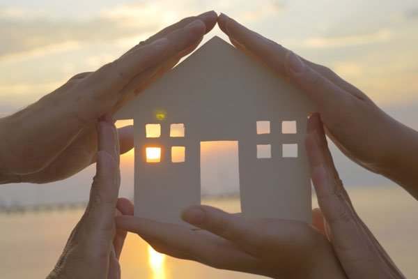 Acosta Law Firm Estate Planning. Close up of two sets of hands holding a cutout of a home