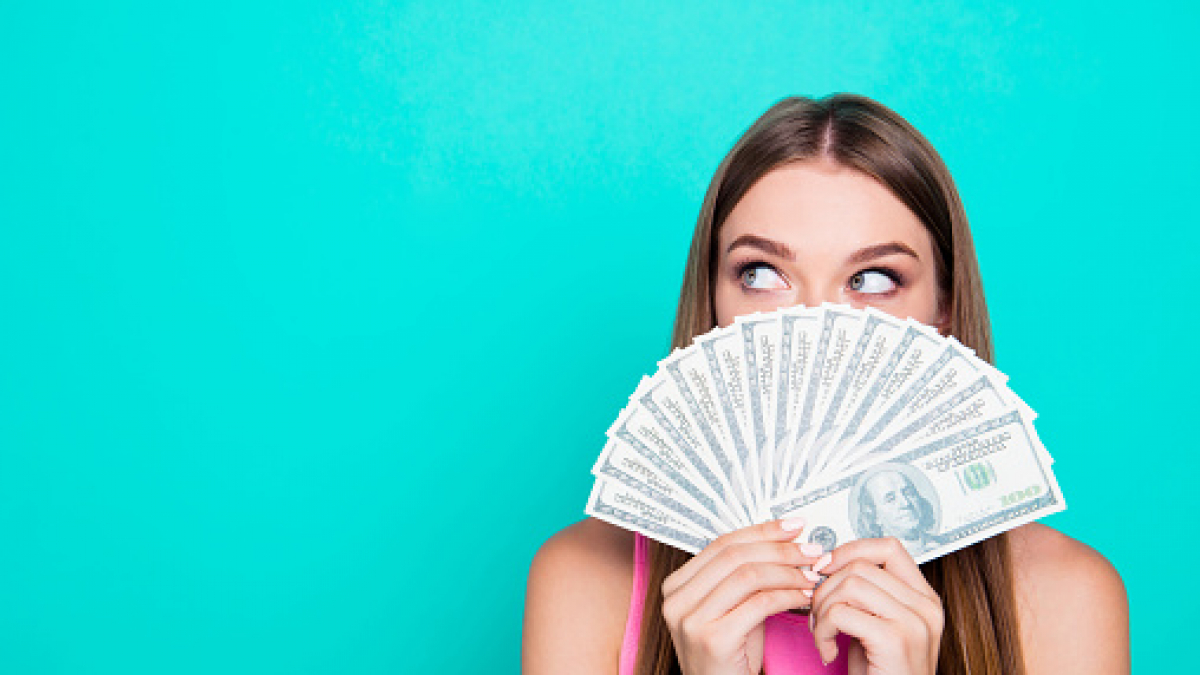 Attractive gorgeous young amazed girl wearing pink blouse, excited, covering face with dollar banknotes. Copy space. Isolated over bright vivid blue teal, turquoise background
