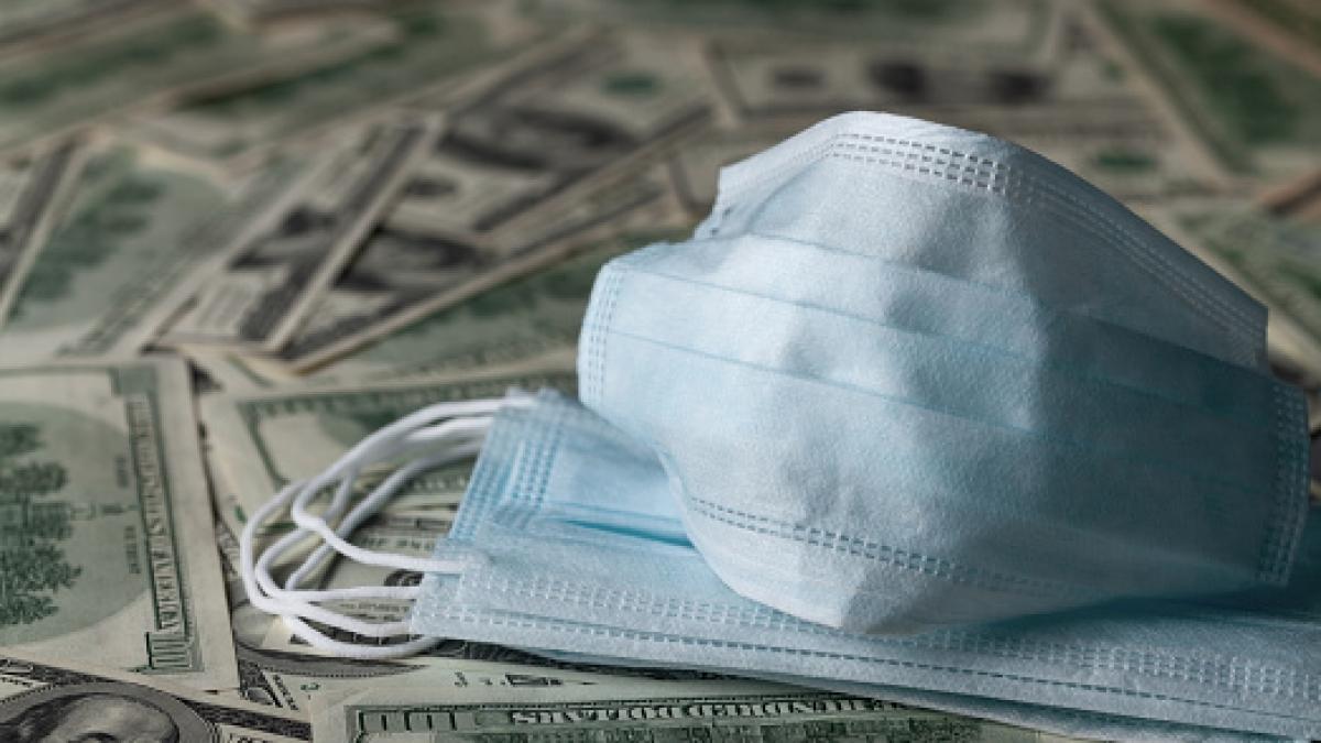 edical face mask and dollar banknotes, world coronavirus epidemic and economic losses concept.