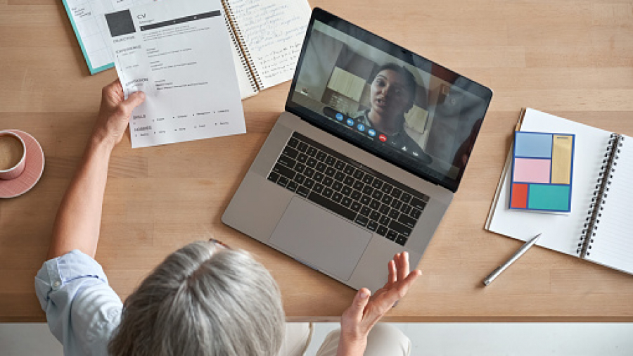 Mature senior employer hr checking indian female job applicant cv holding social distance remote online job interview by video conference call virtual chat meeting with recruit on laptop, top view.